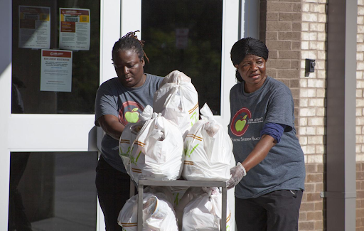 """""""Lunch ladies help by giving out free lunch kits for families during the pandemic."""""""
